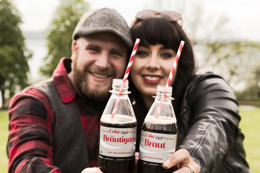 brautpaar haelt coca cola flaschen hoch