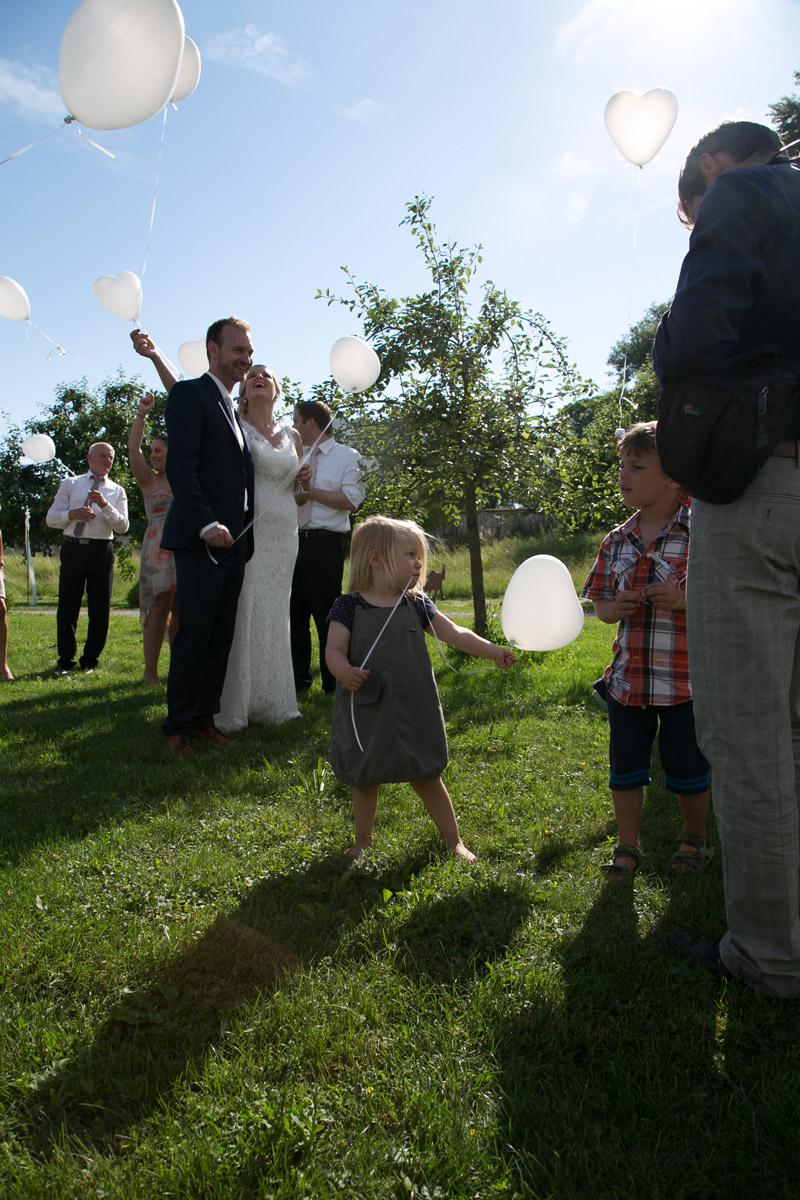 kind und brautpaar mit luftballons