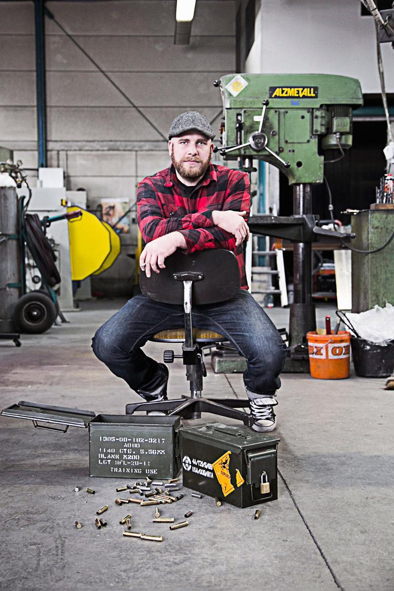 mann sitzt auf hocker in einer werkstatt