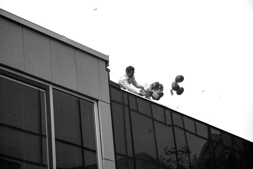 mann haelt luftballons