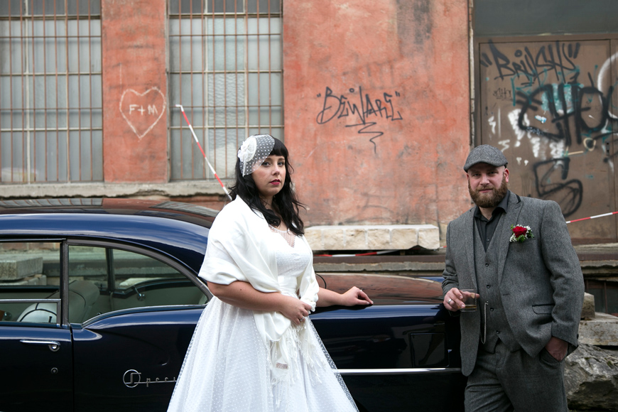 brautpaar steht vor dem hochzeitsauto