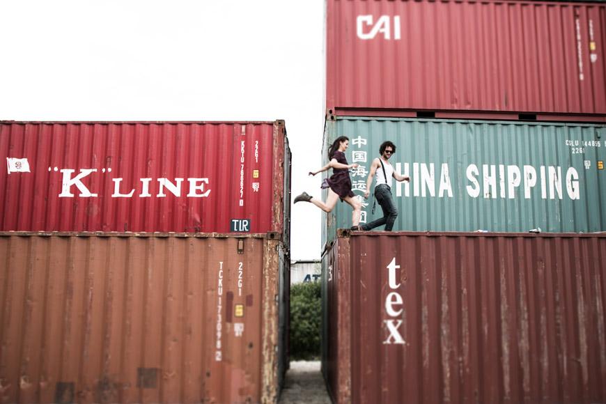 paar springt von kontainer zu kontainer