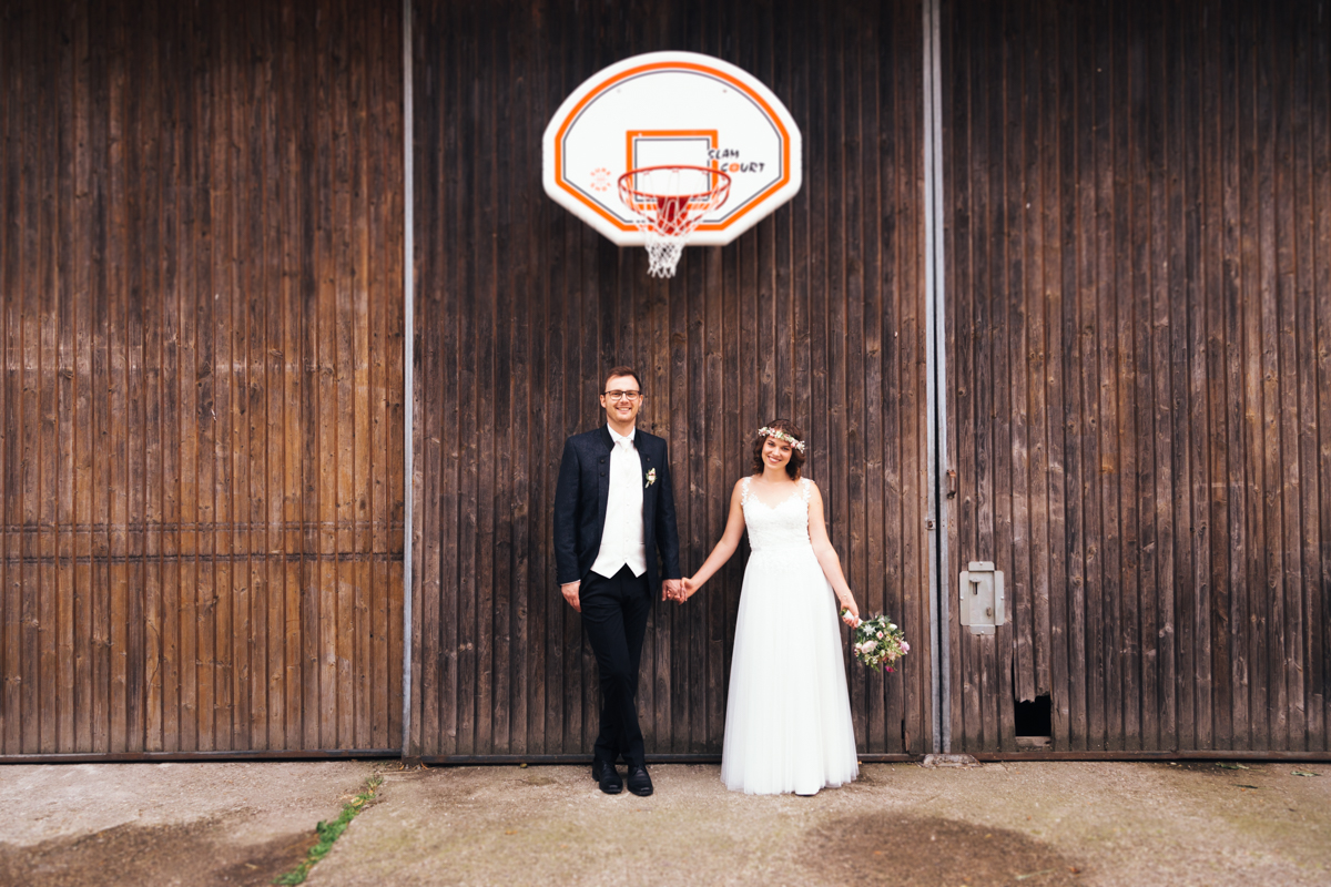 brautpaar steht unter einem basketballkorb
