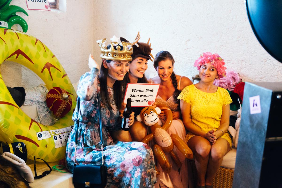 gaeste sitzen verkleidet vor einer photobooth